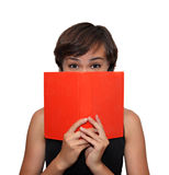 Girl with a book. Young girl higing her face behing an orange book Royalty Free Stock Photos