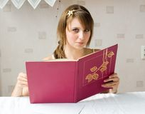 The girl with the book. Behind a table stock photos