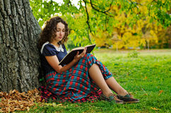 The girl with book. Sitting under the tree Royalty Free Stock Images