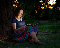 The Girl with Book. Sitting under the tree, twilight. The book is open and emitting a wonderful glow of light Royalty Free Stock Photo