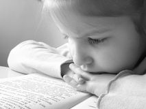 Girl with book 3. Small pretty reading girl black and white portrait Royalty Free Stock Photography