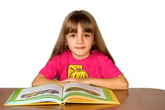 The girl with the book. The girl sits at a table and reads the book with pictures Stock Photos