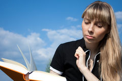 Girl with book. Girl standing with book outdoor with sky in background Stock Images