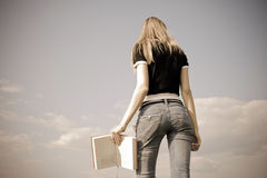Girl with book. Girl standing with book outdoor with sky in background Royalty Free Stock Image