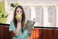 Girl with book and aple outdoors Royalty Free Stock Photos