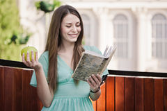 Girl with book and aple outdoors Stock Photos