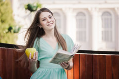 Girl with book and aple outdoors Stock Photo