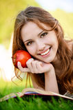 Girl with book and apple Stock Image