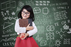 Girl with a book and apple in class Stock Photography