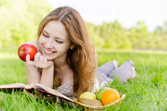 Girl with book and apples Royalty Free Stock Image