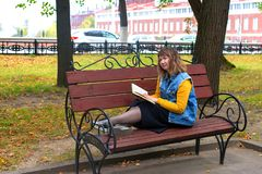 Girl with a book in autumn foliage stock photo