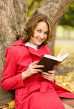 girl with book in the autumn park Royalty Free Stock Image