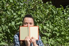Girl with a book on the background of greenery, eyes Stock Photography