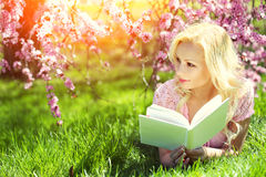 Girl with Book. Blonde Young Woman Lying on the Grass Stock Photos