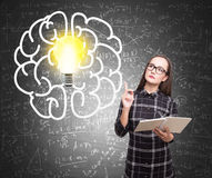 Girl with a book, brain and light bulb Royalty Free Stock Photo
