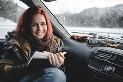 Girl with book in the car. Girl reading book inside the car. Rain drops on the glass stock photo
