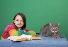 Girl, Book and Cat. A young girl and sits with her cat and a book stock photo