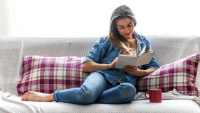 Girl with a book and a Cup on a cozy bed Royalty Free Stock Image