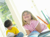 Girl (4-6) with book by friend (4-6), smiling, low angle view (tilt) Royalty Free Stock Photo