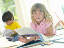 Girl (4-6) with book by friend (4-6), smiling, portrait (tilt) Royalty Free Stock Photos