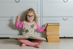 Girl with a book with glasses on the floor, Royalty Free Stock Image