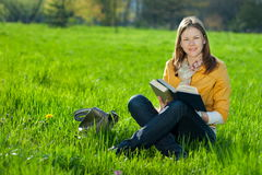 Girl with book on the grass Royalty Free Stock Image