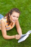 Girl with book on grass Royalty Free Stock Image