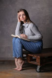 Girl with a book. Gray background Royalty Free Stock Images