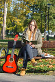Girl, book and guitar on a bench Stock Photo