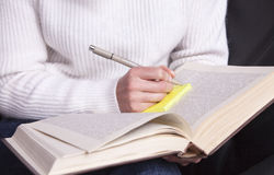 Girl with a book in hand taking notes with a pen. royalty free stock photos