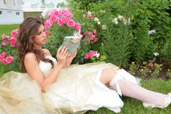 Girl with book in hand under rosebushes Royalty Free Stock Photo