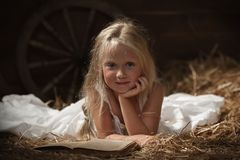 Girl with a book in the hay Royalty Free Stock Image