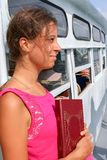 The girl with book in his hand is traveling on white ship. Stock Photos