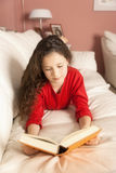 Girl with a book. An image of a girl with a book on the sofa Stock Images
