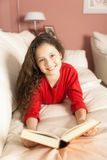 Girl with a book. An image of a girl with a book on the sofa Royalty Free Stock Photo