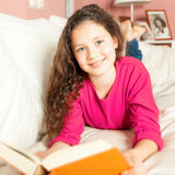 Girl with a book. An image of a girl with a book on the sofa Royalty Free Stock Images