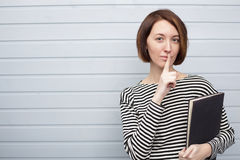 Girl with book keeping silence Stock Photography