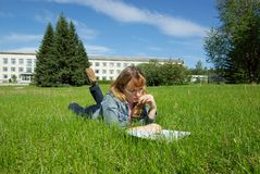 Girl with book lying on grass. Girl reading book and lying on grass and building Stock Image