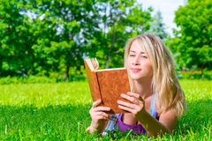 Girl with a book lying on a green meadow Stock Photos