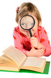 Girl with book and magnifying glass Royalty Free Stock Photo