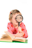 Girl with book and magnifying glass Stock Image