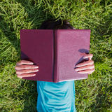 Girl with a book on meadow Royalty Free Stock Images