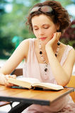 Girl with book outdoors Stock Images