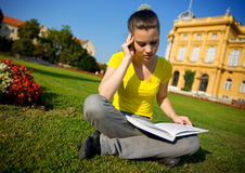 Girl with book in the park stock photos