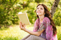 Girl with a book in the park Stock Photos