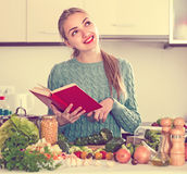Girl with book of recipes at kitchen Royalty Free Stock Photos