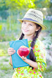 Girl with book and red apple in summer day Stock Photography