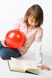Girl with book and red boll Stock Photos