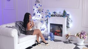 Girl with a book on sofa near the Christmas tree. Gorgeous lady in an evening dress and shoes sitting on the couch with a book on the background of decorated stock video