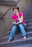Girl with book on the stairs Royalty Free Stock Image